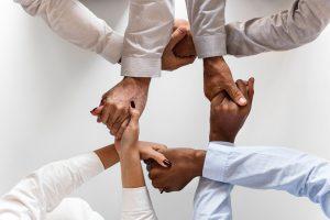 Vista superior de oito mãos dadas, entrelaçadas de forma alternada e em círculo. Todos têm camisas vestidas e são de diferentes etnias e géneros. Apenas se veem as mãos e o antebraço.