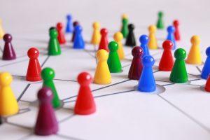 Rede desenhada a negro em papel branco vista em prespectiva em que cada nó da rede está ocupado por um peão de plástico colorido, simbolizando um individuo da rede.